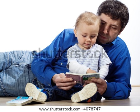 A father reading a book to his young baby son. Isolated on white.