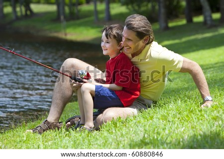 A father teaching his son how to fish on a river outside in summer sunshine - stock photo