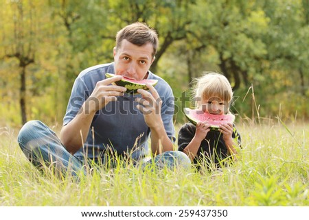 a father with a small daughter eat watermelon on the grass