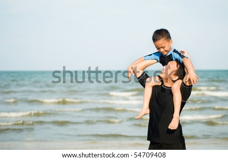 a father with a son on the beach - stock photo