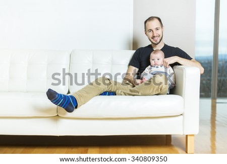 A father with baby on the sofa taking good time - stock photo