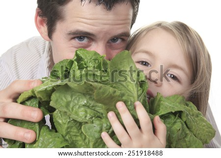 A father with his kid who eating salad - stock photo