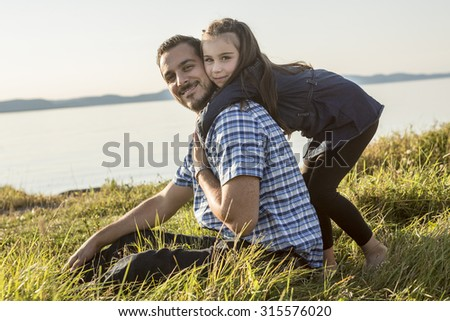 A Father with is daughter at the sunset - stock photo