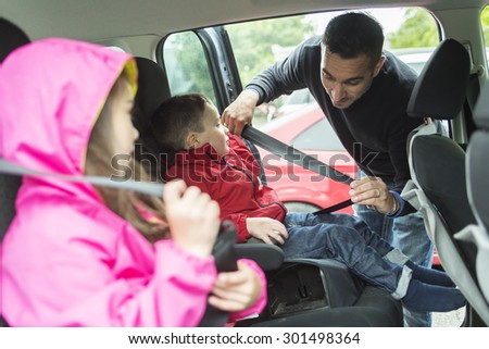 A Father worried about her children's safety in a car - stock photo