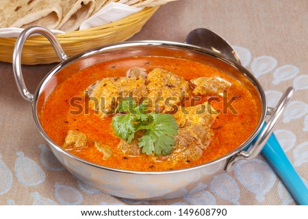 A favourite Indian curry, lamb rogan josh, garnished with coriander, in a balti dish with chapatis in the background. - stock photo