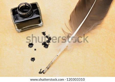 A feather pen, ink, ink blotches on the old yellowed paper. - stock photo