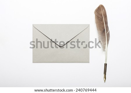A feather quill pen, envelope, isolated white at the studio. - stock photo