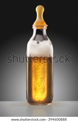 A feeding bottle with nipple full of beer as a milk replacement for babies. - stock photo