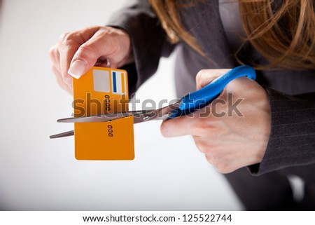 A female about cut up old credit card. - stock photo