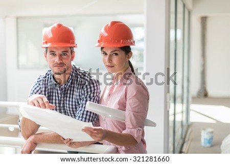 A female architect and a foreman examining blueprints on a construction site. they are standing in a luminous open space, leaning against a white guardrail. They are wearing orange hard hats - stock photo