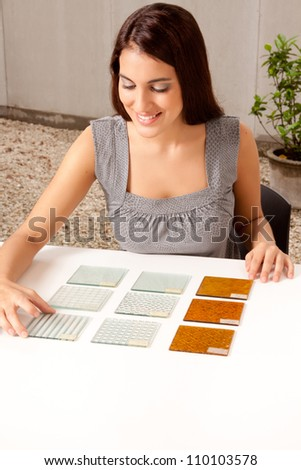 A female architect / designer choosing a glass tile from a group of samples - stock photo
