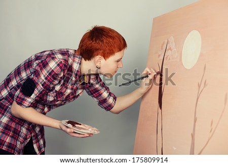 A female artist painting on canvas  - stock photo