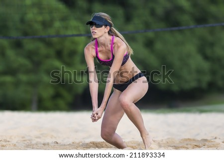 A female beach volleyball athlete on the volleyball court - stock photo