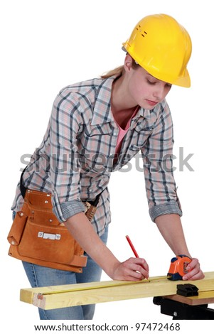 A female carpenter taking measures. - stock photo