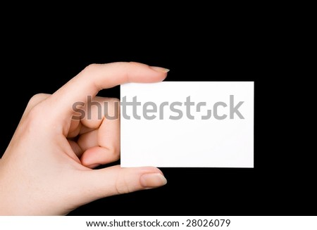 A female Caucasian hand holding a blank white business card between her fingers. Image isolated on black studio background.