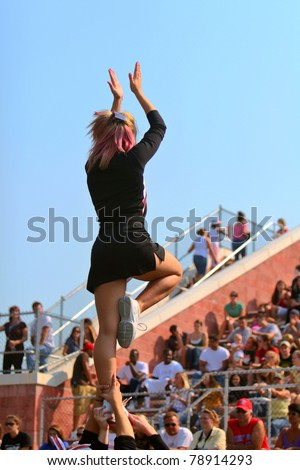 A female cheerleader leads the crowd at a football game.  Copy space across top.