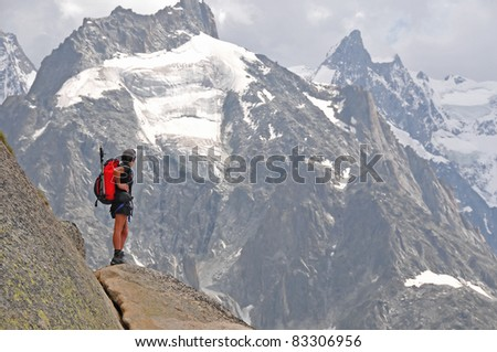 a female climber on a rock face looks across at the surrounding mountains - stock photo