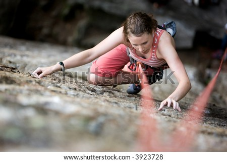 A female climber on a steep rock face viewed from above with the belayer in the background.  Shallow depth of field is used to isolated the climber. - stock photo