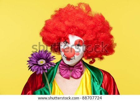a female clown with colorful clothes and makeup holding a flower - stock photo