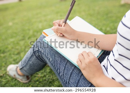 A female college student reading a book while lying on the park - stock photo