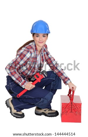 A female construction worker holding a wrench. - stock photo