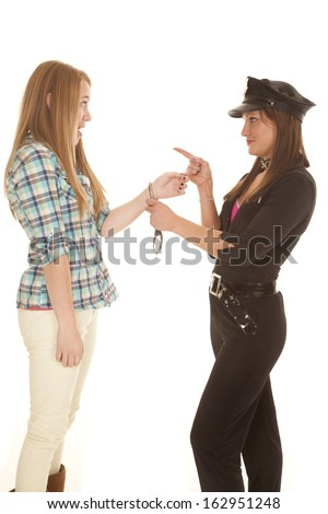 A female cop is pointing at a girl being handcuffed. - stock photo