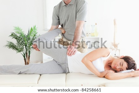 A female customer's leg is stretched by a chiropractor in his surgery - stock photo