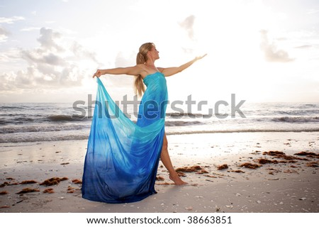 a female dancer is posing in profile with arms raised and looking at her open hand at the beach with brightness of the sun diffusing her hand - stock photo