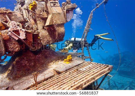 A female diver is exploring the superstructure of the sunken wreck, the Tibbetts, a Russian frigate that was sunk in the waters off Cayman Brac.