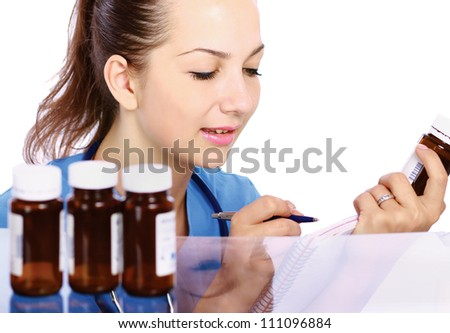 A female doctor holding a bottle pills, isolated on white background