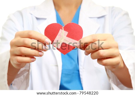 A female doctor holding a wounded paper heart, focus on the heart