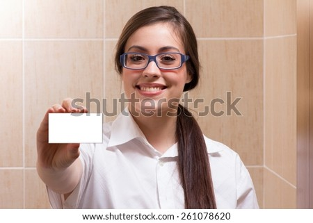 A female doctor holding an empty card with smile on face - stock photo
