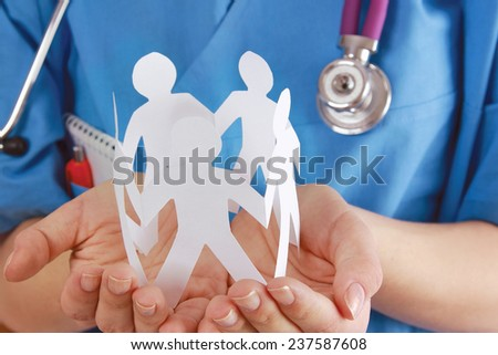 A female doctor holding paper people, focus on the hand - stock photo