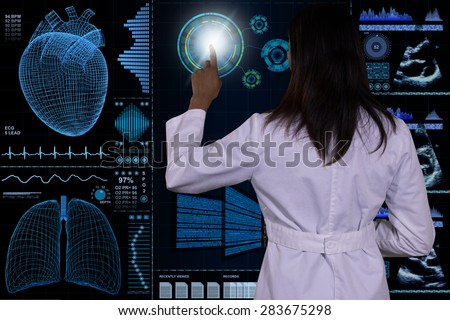 A female Doctor interacts with a futuristic floating glass computer.