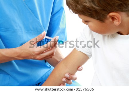 A female doctor is making an injection to the boy, close-up view - stock photo