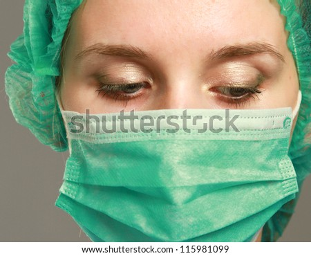 A female doctor wearing a mask, isolated on grey background