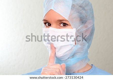 A Female doctor with finger on her lips - stock photo