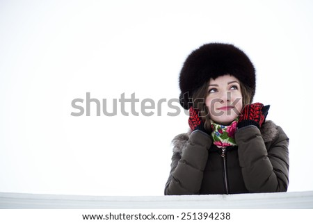 A female dressed in warm clothes curiously looking with a smile - stock photo