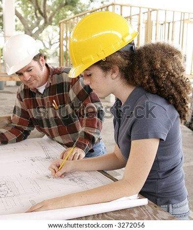 A female engineering student on a construction site marking blueprints as her instructor watches. - stock photo