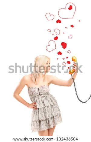 A female giving kisses and holding a telephone tube with red hearts around isolated on white background - stock photo