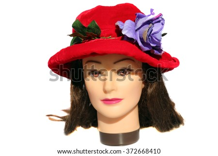A female Hair Dressers Mannequin Head wears a Red Velvet Hat with a Purple Flower.  Isolated on white with room for your text. - stock photo