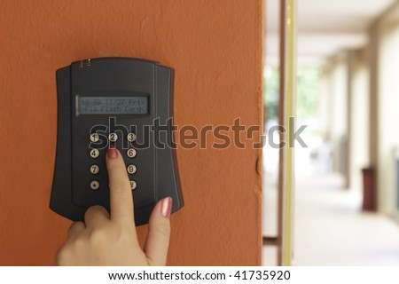 A female hand arming a burglar alarm system mounted on a wall outdoors - stock photo