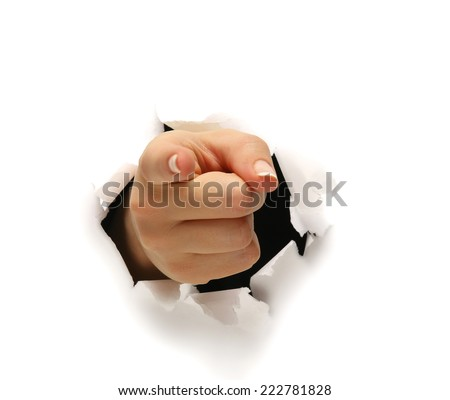 A female hand breaking through paper pointing at you. - stock photo