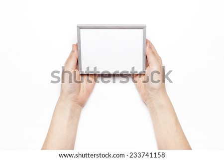 A female hand hold a wood photo(picture) frame isolated white, top view at the studio.