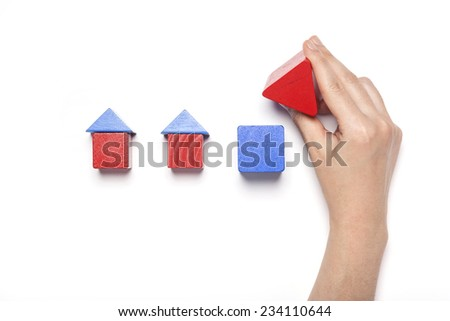 A female hand hold(pick up) red wood block among the red and blue wood blocks like house(real estate) isolated white, top view at the studio. - stock photo