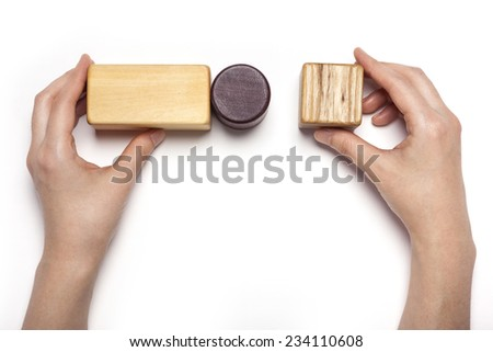 A female hand hold(pick up) the various wood blocks isolated white, top view at the studio. - stock photo