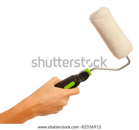 A female hand holding a paint roller on an isolated white background