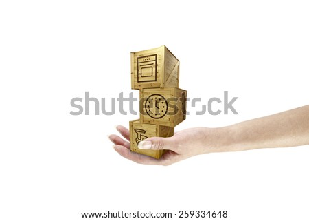A female hand holding a stack of timber crate with cargo prints and symbols for the concept of hand delivery, isolated against white. - stock photo