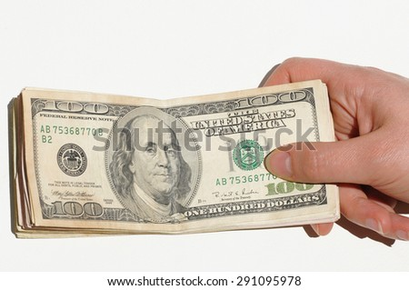 A female hand holding stack of hundreds dollars on white background - stock photo