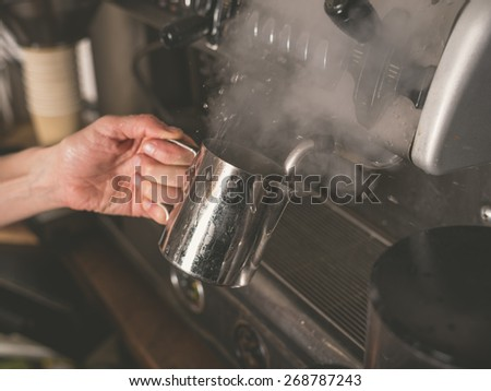 A female hand is placing a cup under the froth element of a professional coffee machine which causes steam to rise from the liquid in the cup